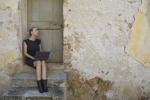 Italy, Tuscany, Monteriggioni, woman sitting at house entrance using laptop - PSTF00299