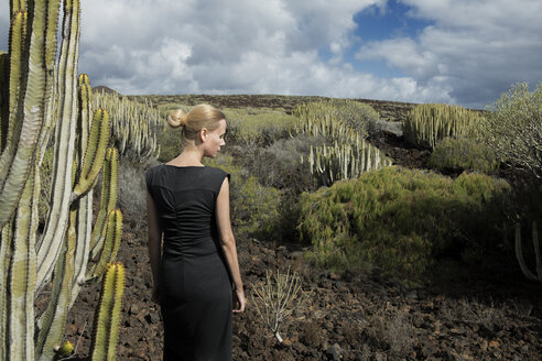 Spain, Tenerife, Malpais de Guimar, woman in volcanic landscape with cacti - PSTF00308