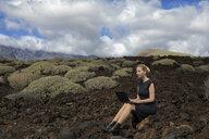 Spain, Tenerife, Malpais de Guimar, woman sitting in volcanic landscape with cacti using laptop - PSTF00311