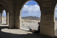 Spain, Tenerife, Abades, Sanatorio de Abona, woman sitting at arched window in ghost town building - PSTF00317