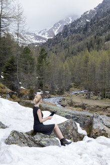 Italy, Alto Adige, Ultental, woman sitting in snow-capped mountain valley using tablet - PSTF00320