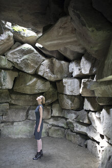 Italy, Alto Adige, Lana, woman standing in stone cave looking up - PSTF00323