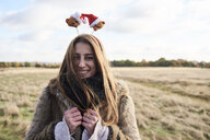 Portrait of happy young woman wearing Christmassy headdress in the countryside - IGGF00828