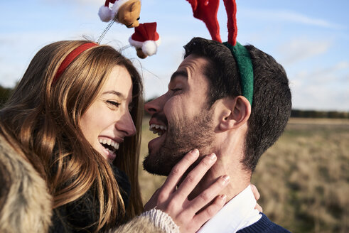 Happy carefree couple wearing Christmassy headdress in the countryside - IGGF00831