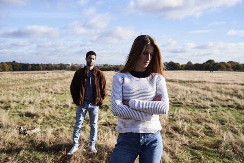 Serious young woman standing on a field with man behind her - IGGF00837