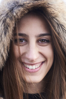 Portrait of happy young woman wearing fur hood - IGGF00840