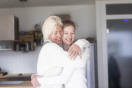 Portrait of happy mother embracing  adult daughter at home - SGF02292
