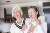 Portrait of happy mother embracing her adult daughter - SGF02298