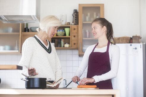 Mutter und Tochter zusammen zu Hause kochend - SGF02313