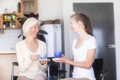 Mother and daughter with coffee cups, mother in wheelchair - SGF02328