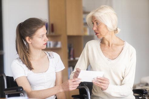 Mutter und Tochter im Rollstuhl sitzend mit Karte - SGF02331