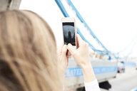 UK, London, woman taking photo with smartphone of Tower Bridge - IGGF00844