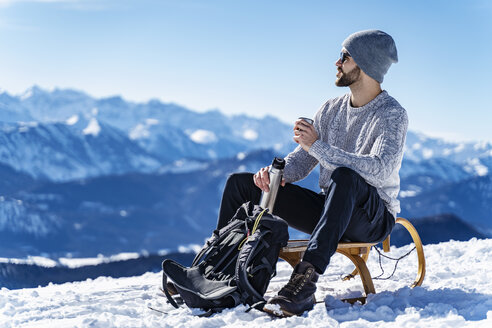 Germany, Bavaria, Brauneck, man in winter in the mountains having a break - DIGF05905