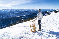 Germany, Bavaria, Brauneck, man with sledge in winter in the mountains looking at view - DIGF05914