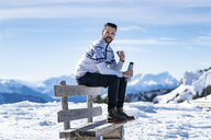 Germany, Bavaria, Brauneck, man sitting on bench in winter in the mountains having a break - DIGF05917