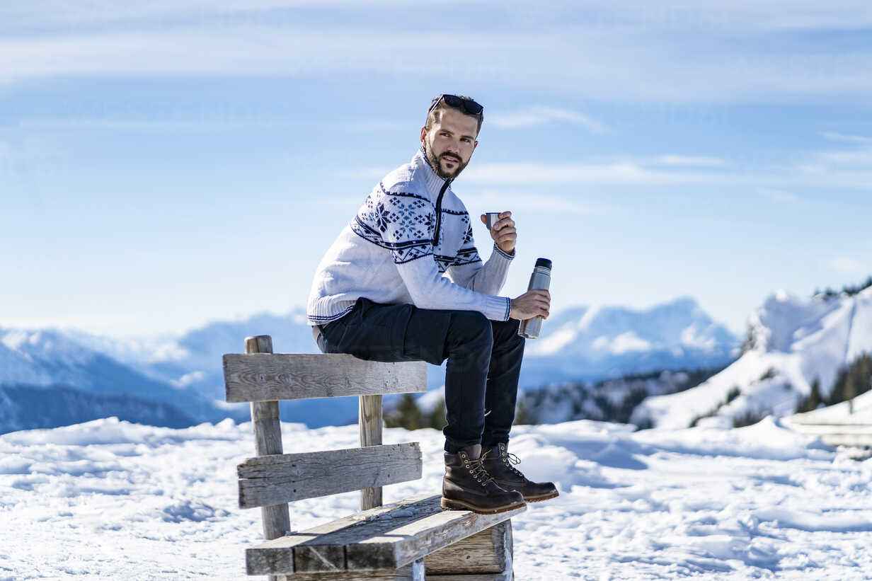Germany, Bavaria, Brauneck, man sitting on bench in winter in the mountains having a break - DIGF05917 - Daniel Ingold/Westend61