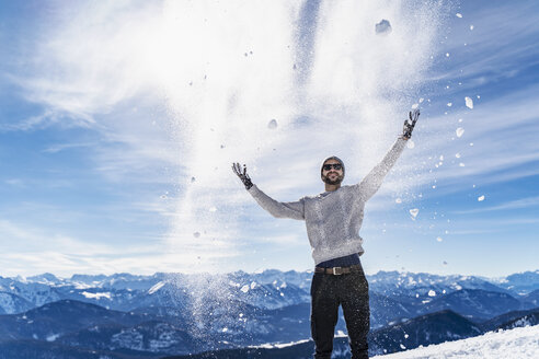 Germany, Bavaria, Brauneck, man in winter playing with snow in the mountains - DIGF05932