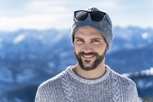 Germany, Bavaria, Brauneck, portrait of smiling man in winter in the mountains - DIGF05935
