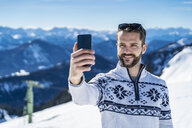 Germany, Bavaria, Brauneck, man in winter in the mountains taking a selfie - DIGF05938
