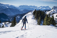 Germany, Bavaria, Brauneck, man on a ski tour in winter in the mountains - DIGF05941