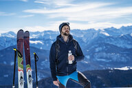 Germany, Bavaria, Brauneck, man on a ski tour in winter in the mountains having a break - DIGF05959