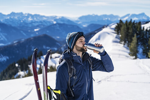 Germany, Bavaria, Brauneck, man on a ski tour in winter in the mountains having a break drinking from thermos flask - DIGF05962