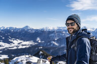 Germany, Bavaria, Brauneck, portrait of smiling man on a ski tour in winter in the mountains - DIGF05965