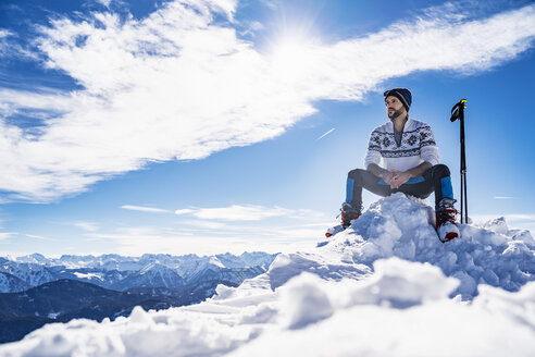Germany, Bavaria, Brauneck, man in winter sitting on mountaintop - DIGF05968