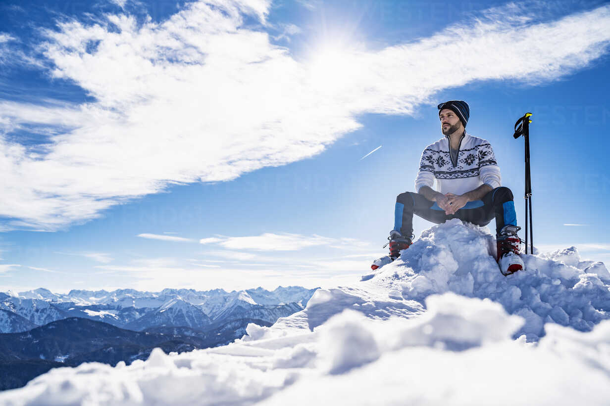 Germany, Bavaria, Brauneck, man in winter sitting on mountaintop - DIGF05968 - Daniel Ingold/Westend61