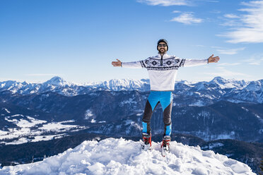 Germany, Bavaria, Brauneck, happy man in winter standing on mountaintop - DIGF05971