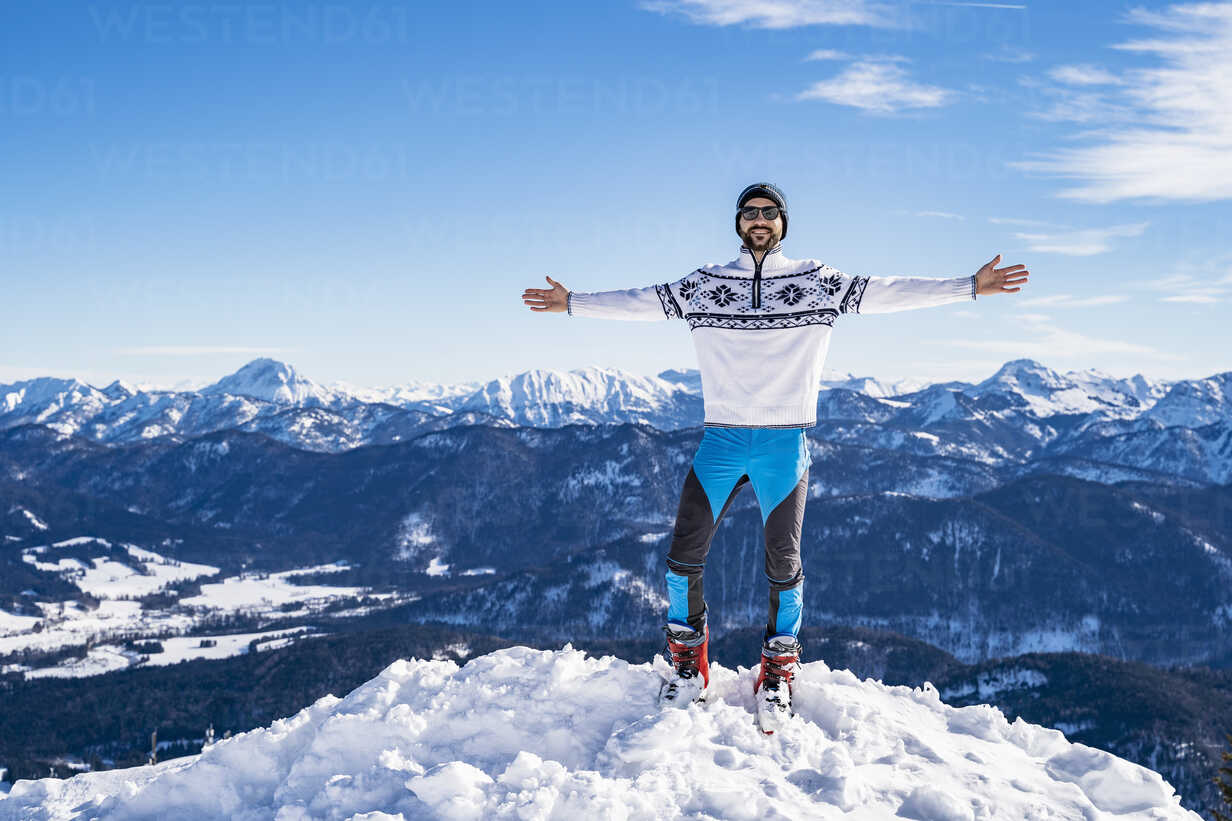 Germany, Bavaria, Brauneck, happy man in winter standing on mountaintop - DIGF05971 - Daniel Ingold/Westend61