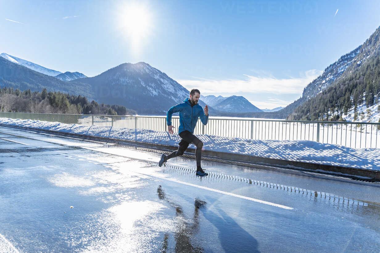 Germany, Bavaria, sportive man running on a road in winter - DIGF05974 - Daniel Ingold/Westend61