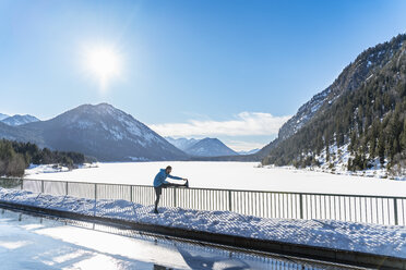 Germany, Bavaria, sportive man stretching in winter on bridge railing - DIGF05977