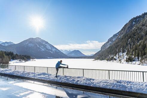 Germany, Bavaria, sportive man stretching in winter on bridge railing - DIGF05977