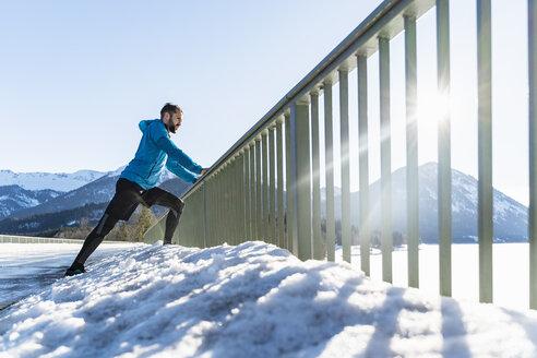 Germany, Bavaria, sportive man stretching in winter on bridge railing - DIGF05980