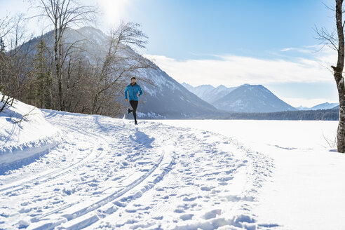 Germany, Bavaria, sportive man running through snow in winter - DIGF05983