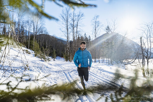 Germany, Bavaria, sportive man running in winter - DIGF05992