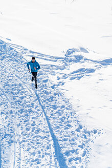 Germany, Bavaria, sportive man running through snow in winter - DIGF05995