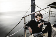Businessman on a houseboat using laptop and smartwatch, wearing headphones - MJRF00077