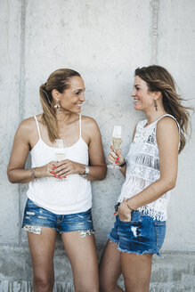 Two best friends drinking champagne outdoors - HMEF00237