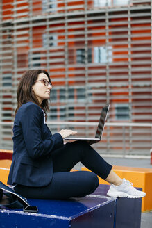 Businesswoman sitting outside office building in the city using laptop - JRFF02729
