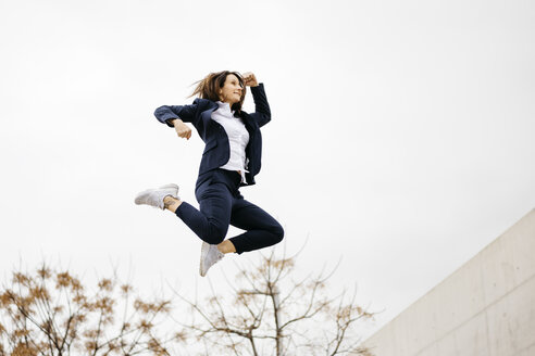 Happy businesswoman jumping in the city - JRFF02753