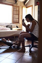 Mother playing guitar to little boy at home - IGGF00860