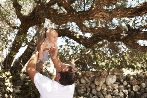 Father playing with little boy outdoors under a tree - IGGF00869