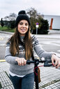 Portrait of smiling young woman with electric scooter in the city - MGOF03954