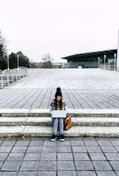 Young woman sitting outdoors on stairs using laptop - MGOF03957