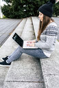 Young woman sitting outdoors on stairs using laptop - MGOF03960