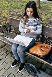 Young woman sitting outdoors on a bench using smartphone and laptop - MGOF03969