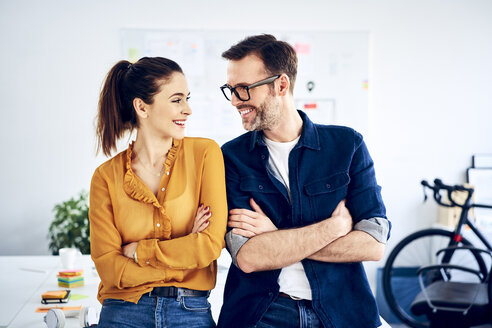 Two smiling colleagues in office facing each other - BSZF01023