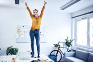 Happy young businesswoman cheering in office standing on desk - BSZF01029